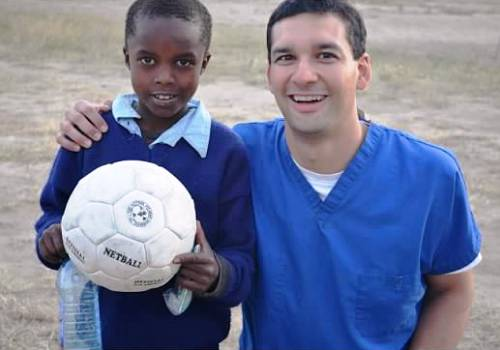 Mission Trip - Dr. Vostatek and boy with soccer ball